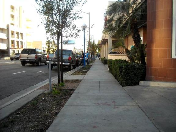 La Brea Avenue, looking south: Same gloomy sidewalk. Non-descript trees (albeit drought-resistant). Landscaping barely improved.