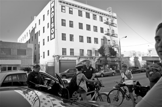 A ride marshal from Clitoral Mass is ticketed for running a red light. Sahra Sulaiman/Streetsblog LA