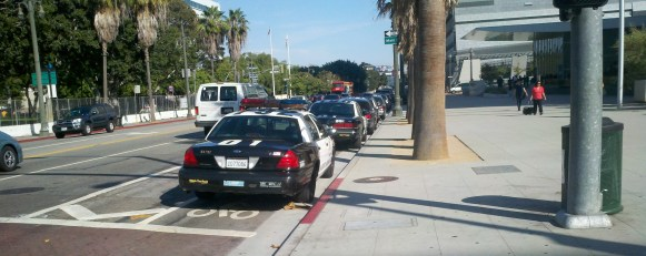 LAPD protects the bike lane in front of headquarters from sun and rain elements that could damage the paint job. Police cars parked in the bike lane, First Street between Spring and Main in downtown L.A.