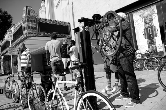 Ade Neff of the Ride On! bike co-op puts his bike up on the stand at the repair station outside the KAOS Network in Leimert Park as members of Black Kids on Bikes gather for their monthly ride. Sahra Sulaiman/Streetsblog L.A.