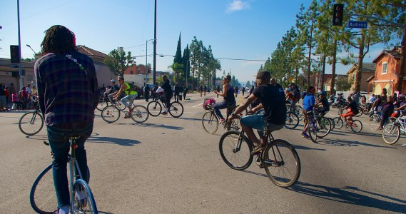 A rider performs a track stand while others loop around and head back down the boulevard. Sahra Sulaiman/Streetsblog L.A.