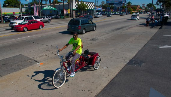 Fred Buggs, president of the East Side Riders and builder of incredible bikes, heads back toward an intersection to help shepherd rides through it. Sahra Sulaiman/Streetsblog L.A.