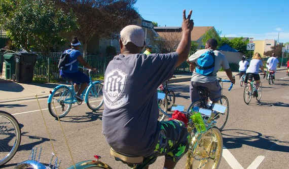 """Tyrone """"T-money"""" Williams of the South L.A. Real Rydaz waves to Watts residents. Sahra Sulaiman/Streetsblog L.A."""