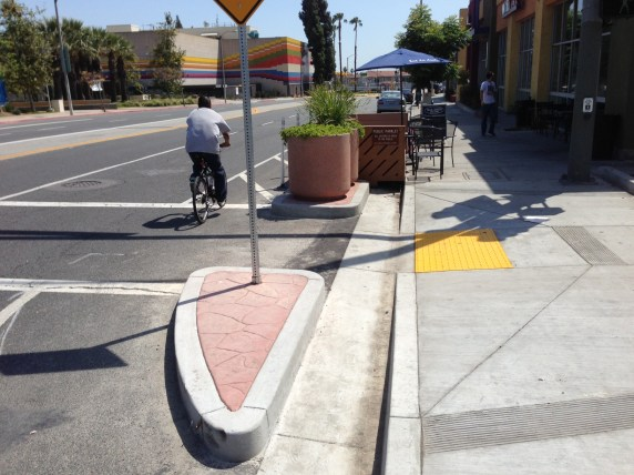 Curbs and planters prevent drivers from colliding with the Mednik parklet