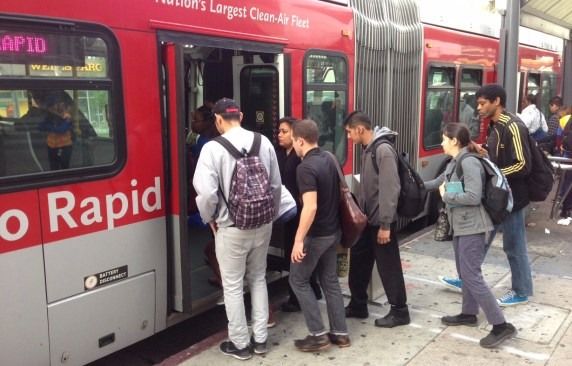 Riders getting on the back door of the Metro 720 bus