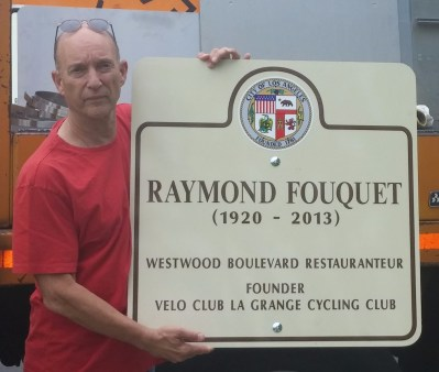 Former La Grange and City Bicycle Advisory Committee head Jay Slater with city signage for Raymond Fouquet Square commemoration. Photo via La Grange