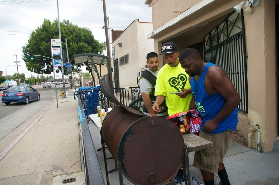 Chucc Standokes and John Jones fire up the grill while Miguel Partida of Los Ryderz looks on. Sahra Sulaiman/Streetsblog L.A.