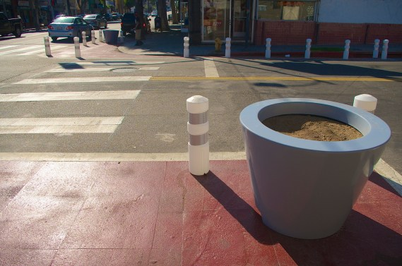 A planter sits empty at Cesar Chavez and St. Louis, while bollards across the street appear to block the fire hydrant. Sahra Sulaiman/Streetsblog L.A.