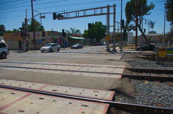 As you step onto the tracks at 48th St., the pedestrian signal is both far away and disappears behind signage. Sahra Sulaiman/Streetsblog L.A.