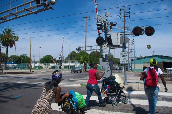 A family with small children moves across the tracks at 55th and Long Beach Ave. Sahra Sulaiman/Streetsblog L.A.