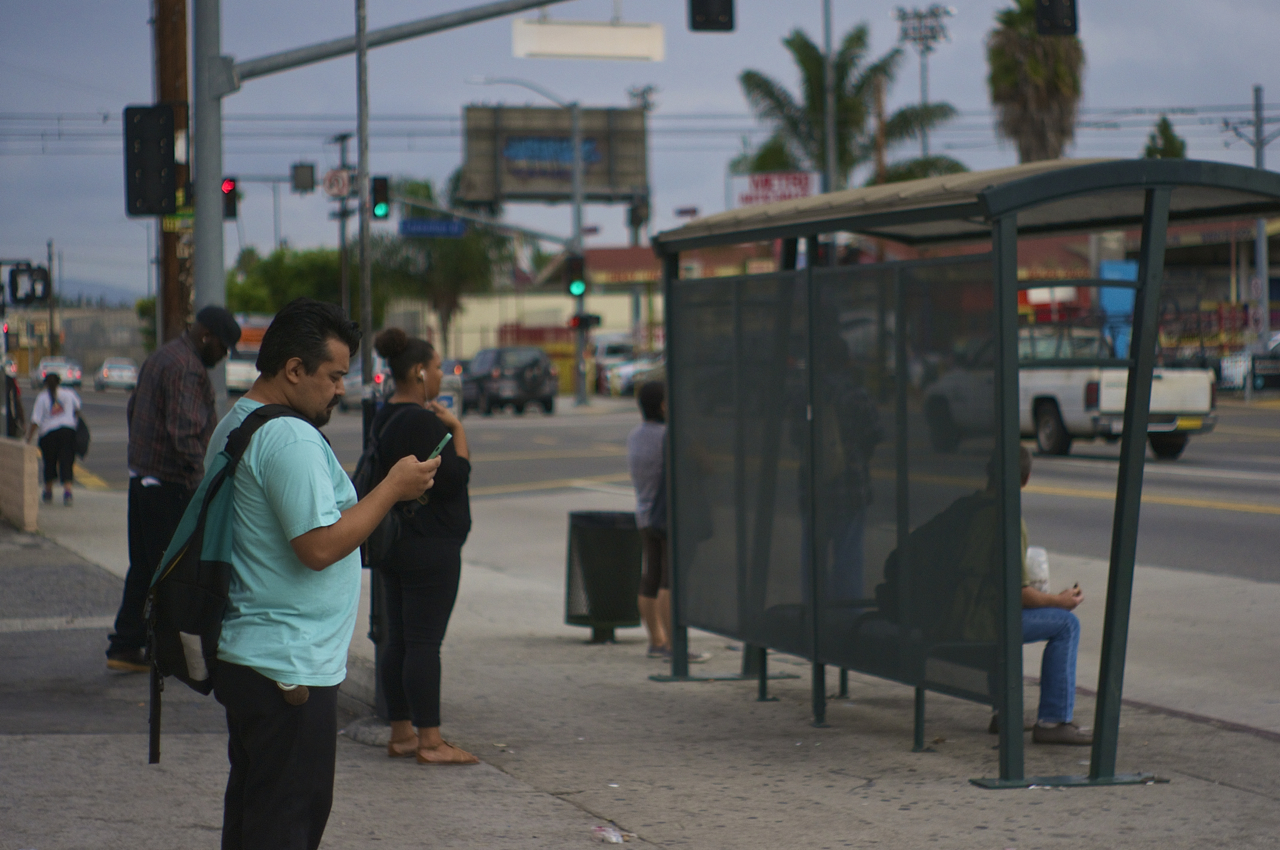 Erick Huerta checks his phone as he waits for the bus on Western Ave. at Exposition Blvd. At this point he has already taken one bus and one train and has been in transit for an hour and fifteen minutes. Sahra Sulaiman/Streetsblog L.A.