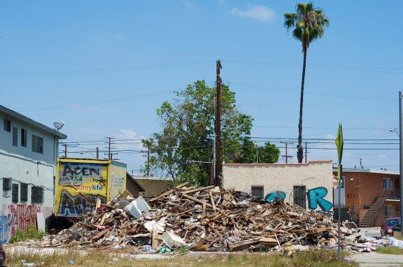 A two-story apartment building in Watts burned down over a year ago. The collapsed structure has yet to be cleared from the lot. Sahra Sulaiman/Streetsblog L.A.