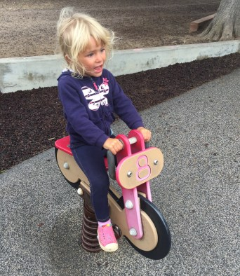 Maeve riding the playground bike