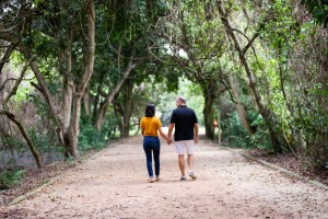 Juliana Frota e Nelson Paiva andando de mãos dadas no Bosque da Barra, no Rio de Janeiro