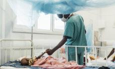 Sairaalasängyssä makaava lapsi pitää hoitajan kädestä kiinni