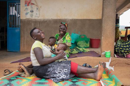 Kaksi naista istuvat sairaalan pihalla. Kummallakin on sylissään vauva.