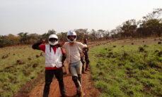 Toisiinsa nojailevat miehet näyttävät peace-merkkiä. Heillä on päässään moottoripyöräkypärät ja he seisovat mutaisella polulla keskellä peltoa.