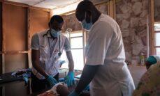 Kaksi lääkäriä tutkivat tutkimuspöydällä makaavaa lasta.