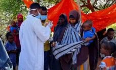 Valkoiseen kaapuun ja kasvomaskiin pukeutunut mies jakaa pieniä pähkinätahnapusseja hänen ympärilleen kokoontuneelle joukolle naisia ja lapsia.