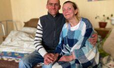 Mies ja nainen istuvat vierekkäin ja pitävät toisiaan kädestä kiinni. Miehellä on käsi naisen ympärillä, ja kumpikin hymyilee.