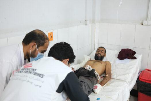 Kaksi miestä hoitaa paareilla makaavaa loukkaantunutta miestä. Miehen verinen käsi on paketoitu.