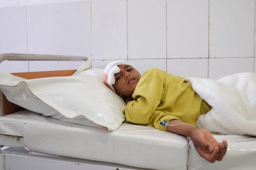 Poika makaa sairaalasängyssä. Hänen päänsä ympärillä on kääreitä.