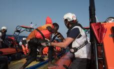 Avustustyöntekijä avustaa miestä nousemaan puisesta veneestä pelastusveneeseen.