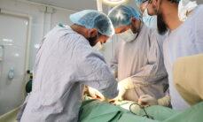 Kolme sairaanhoitohenkilökunnan jäsentä suorittavat leikkausta.