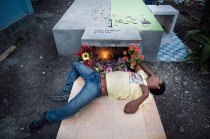Un hombre queda dormido en una lápida después de velar a sus familares y beber canelazo. Foto: Edu León