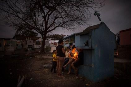 Se encienden velas ante las lapidas maltrechas del cementerio. Foto: Edu León