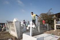 Jóvenes juegan sobre las lápidas del cementerio de Pedernales.