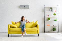 beautiful young woman sitting on yellow sofa under air conditioner in spacious apartment