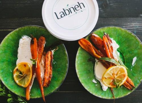 Labneh op twee groene borden met geroosterde wortelen, schijfjes citroen en harissa-olie
