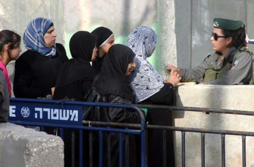 Israeli border policemen check the IDs of the Palestinian female worshippers