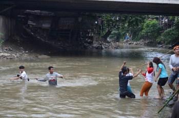 Warga menggunakan tali tambang sebagai alat bantu menyeberangi sungai.