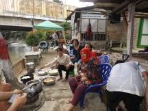 Masyarakat memasak makan siang di pinggir sungai.