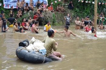 Pencari butut melintas di Kampung Aur saat perlombaan panjat pinang berlangsung