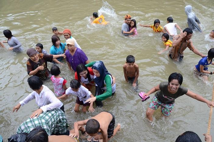 Seorang warga menggendong anaknya bersamaan dengan peserta lainnya meninggalkan sungai.