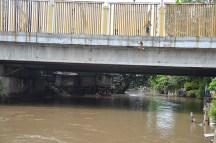 Seorang anak telanjang melimpat dari atas jembatan