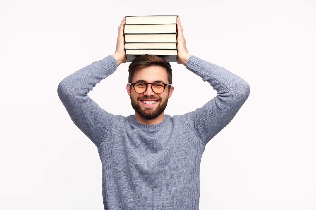 Smiling diligent student with stack of books