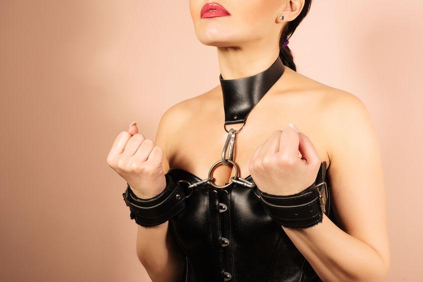 femme attaché depuis son corset à son collier et à ses menottes pour une soumission totale.