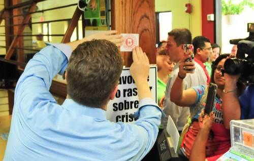 Momento en que el doctor David Bernier personalmente coloca propaganda en uno de los puestos de la Plaza del Mercado de Mayagüez (Suministrada Comité Bernier).