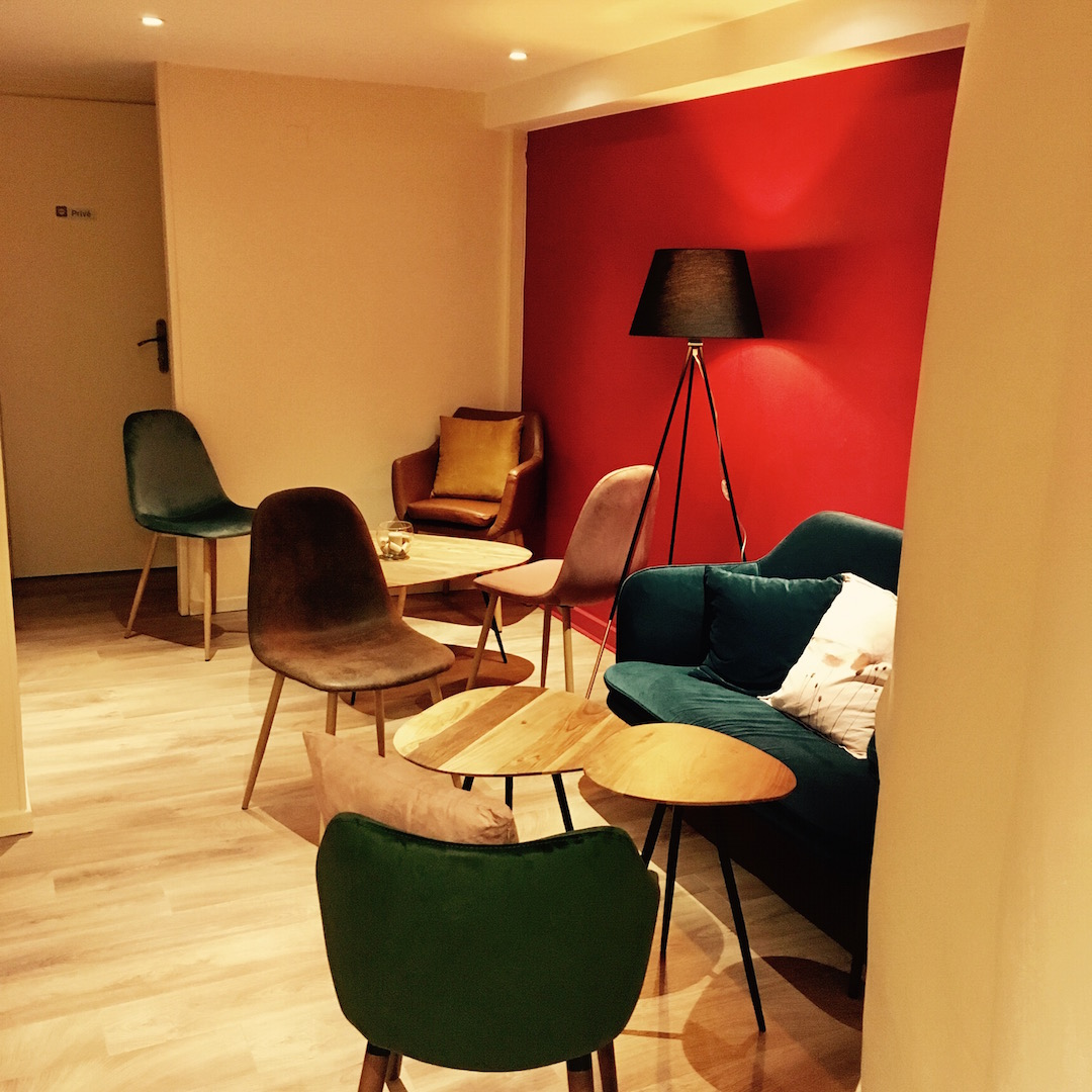 Salon à l'arrière -Perfect to enjoy a late morning coffee or early afternoon vins naturels - small green couch on a red wall with warm yellow light surrounded by comfy chairs with cushions and small wooden tables