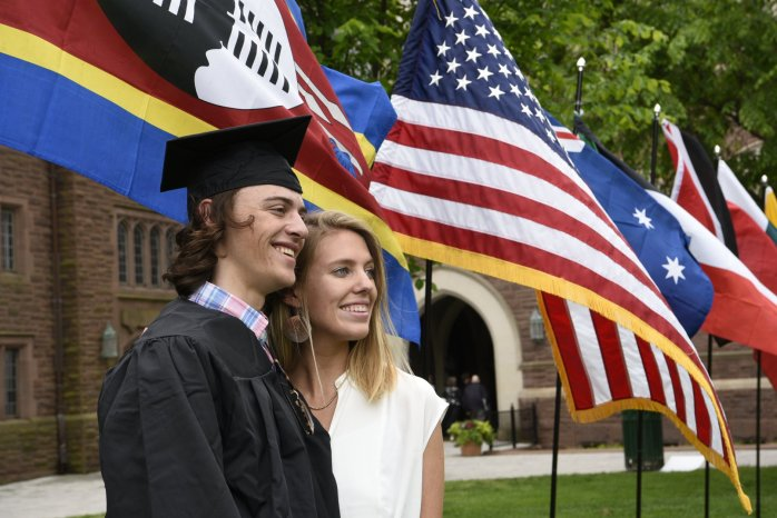 Tim and Haley on commencement day standing in front of the flags of Eswatini, USA and Australia.