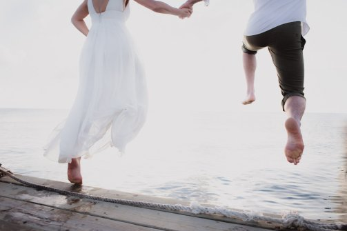 bride and groom jump into water
