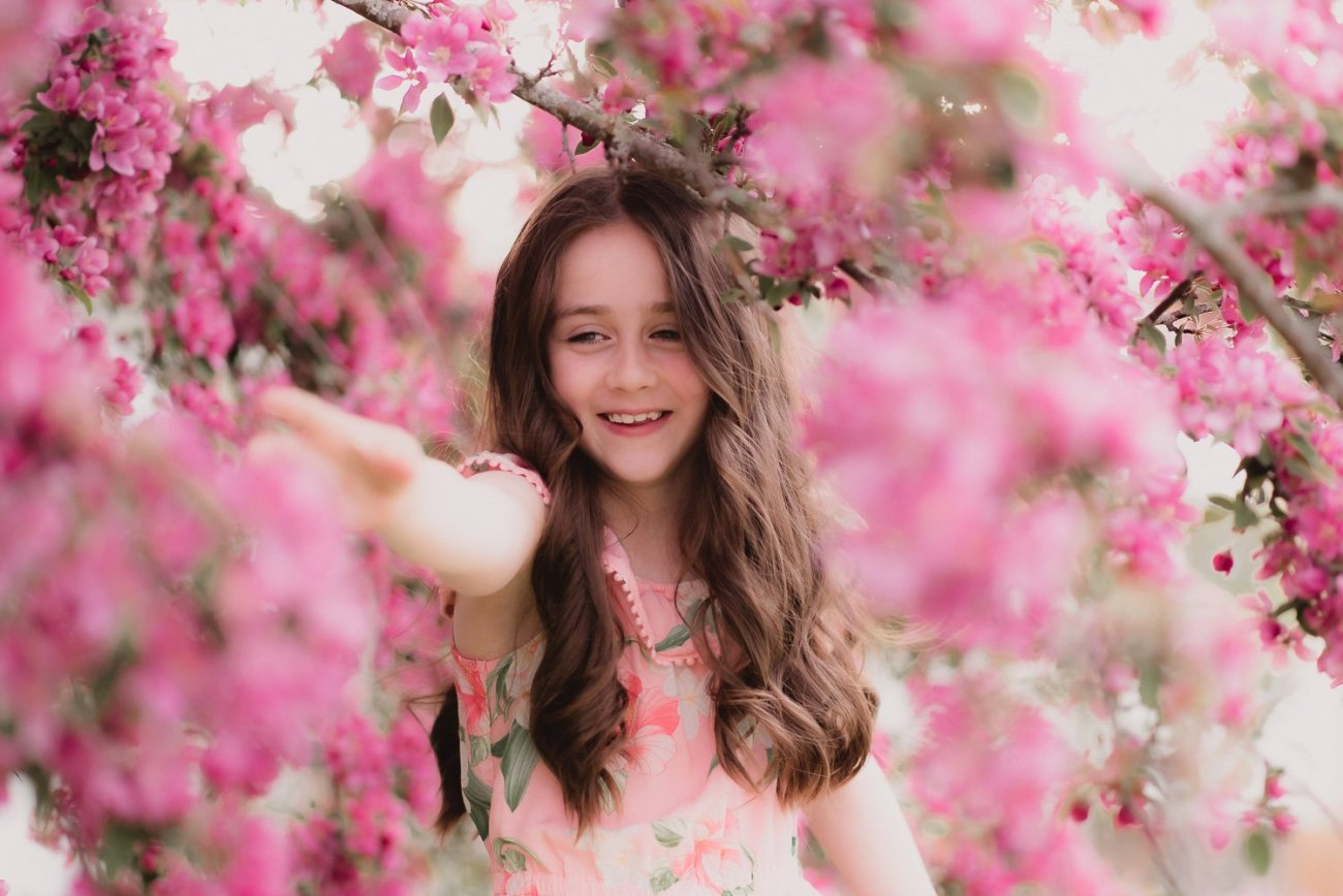young girl smiles at flowers