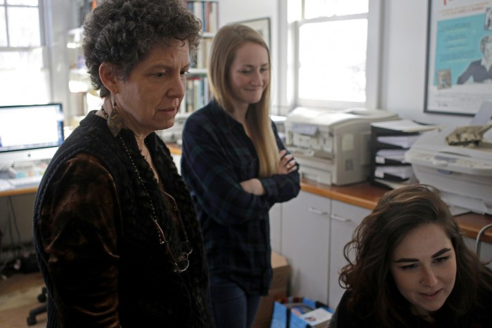 Laurie Kahn (left) looking at pictures with production assistant Riley Davis (center) and production coordinator Julia Hines. Photo: Sean Proctor/Boston Globe