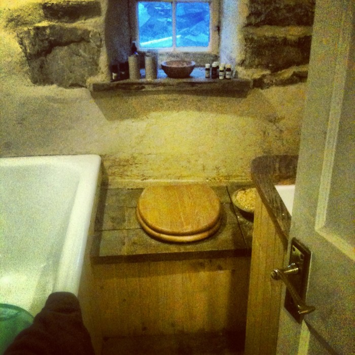 The bathroom - recycled bath and sink; second hand floor, composting toilet made from old roof timbers.