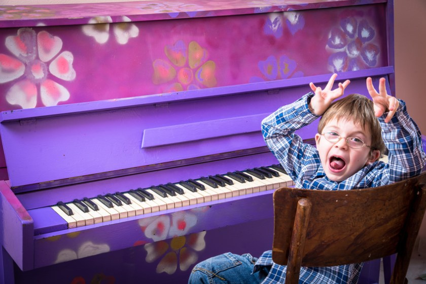 Little boy with glasses playing the piano
