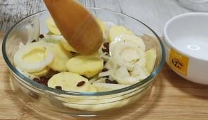 Lubina pescado en el horno con patatas, cebolla, pasas y jamón.